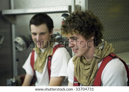 Two young Firemen talking about the fire - stock photo