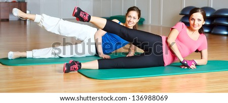 two young fitness woman doing exercises in sports club