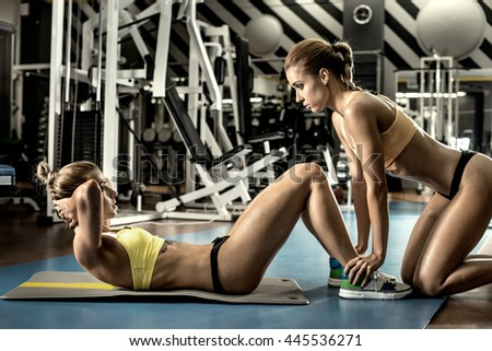 two young fitness woman, execute exercise on prelum abdominale in gym, horizontal photo - stock photo