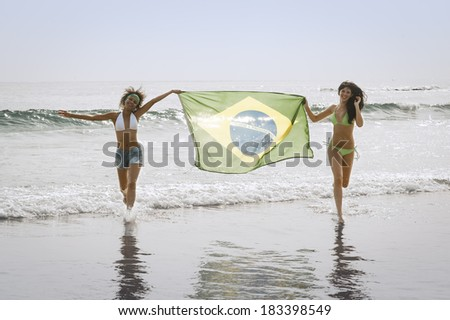 Two young football supporters running though surf with Brazil flag - stock photo