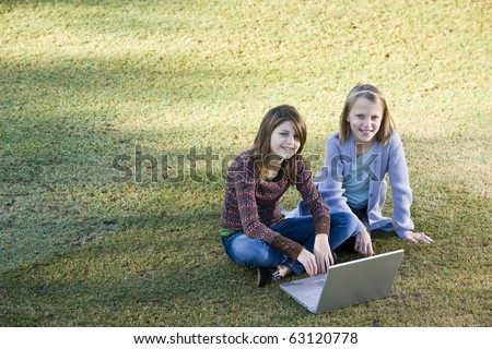 Two young friends (10 and 11 years) using laptop together outdoors in park