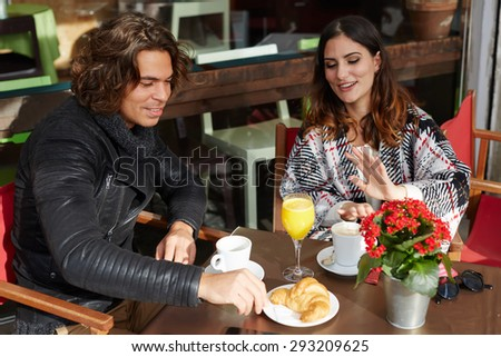 Two young friends enjoying their breakfast in a beautiful sidewalk coffee shop at autumn day, beautiful couple talking to each other and smiling while spending time together at a restaurant outdoors - stock photo
