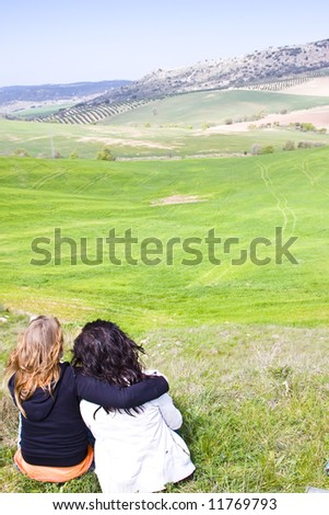 Two young friends looking rural landscape - stock photo