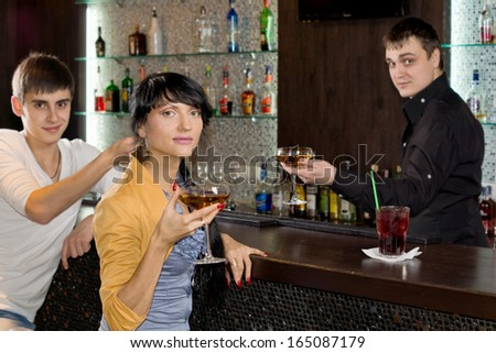 Two young friends relaxing in a pub sitting drinking glasses of red wine at a bar counter with the barman working alongside them - stock photo