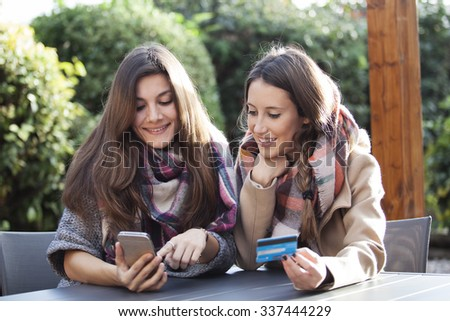 Two young friends shopping on line with a credit card and phone - stock photo