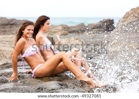 two young friends sitting together laughing on rock at the beach - stock photo
