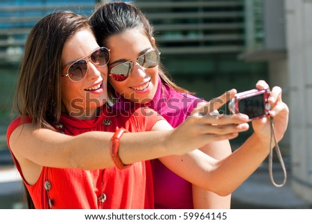 two young friends taking a picture in the park - stock photo