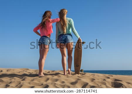 two young friends with jeans playing on beach - stock photo