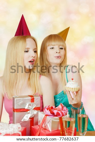 Two young girl at birthday party with gift box and cake - stock photo
