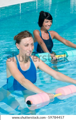 Two young girl doing aqua gym exercise with water dumbbell in a swimming pool