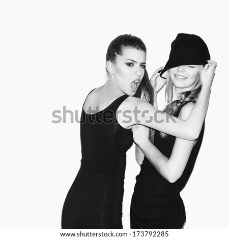 Two young girl friends have a quarrel (having fun). Brunette pulling blonde's beanie. Blonde smiling. Casual style. Inside.