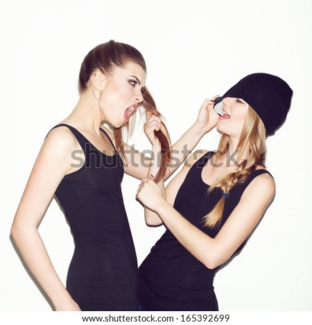 Two young girl friends having a quarrel. One keeping brunette's hair. Second pulling blonder's hat - stock photo