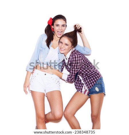 Two young girl friends having fun  and smiling, making hairdo. White background, not isolated
