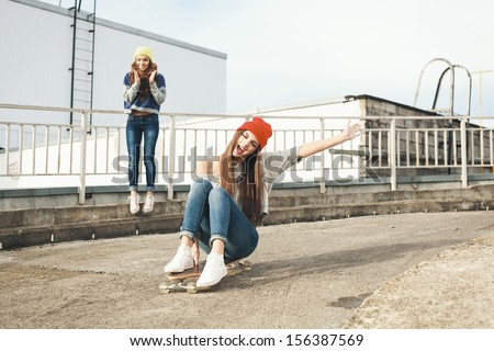 Two young  girl friends having fun. Downhill, longboarding . Outdoors, lifestyle.