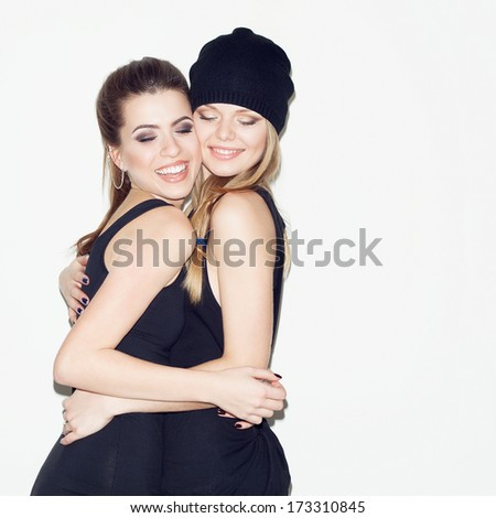 Two young girl friends having fun together. Hugging each other and smiling. Casual style. Inside - stock photo