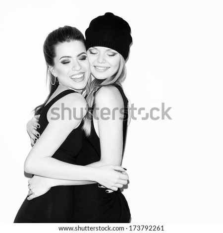 Two young girl friends having fun together. Hugging each other and smiling. Eyes closed. Casual style. Inside - stock photo