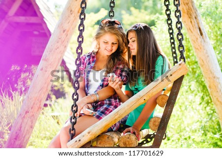 Two young girl friends sitting on swings in park outdoors and looking on mobile phone on the bright day of summer background - stock photo