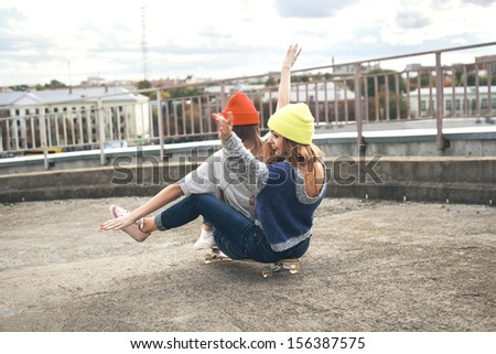 Two young  girl friends sitting together on long-board and having fun. Downhill, longboarding . Outdoors, lifestyle. - stock photo