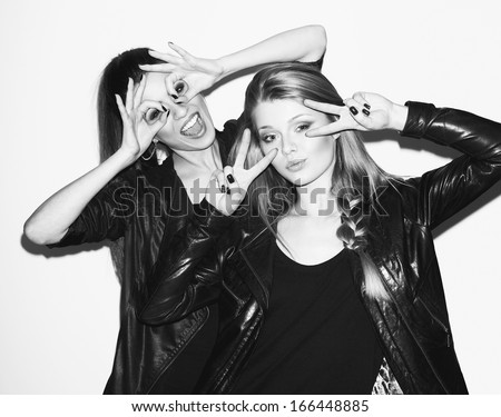 Two young girl friends standing together and having fun. Both showing signs with their hands. Looking at camera. Inside - stock photo