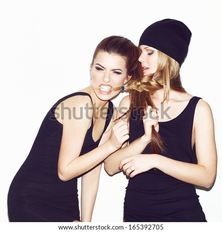Two young girl friends standing together and having fun. Inside. Bright makeup.  - stock photo