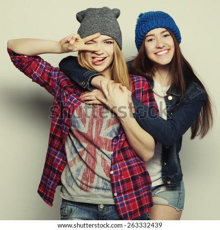 two young girl friends standing together and having fun. Showing signs with hands. Looking at camera - stock photo