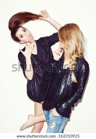 Two young girl friends standing together. Brunette having fun. Blonde showing sign with her hand. Inside - stock photo