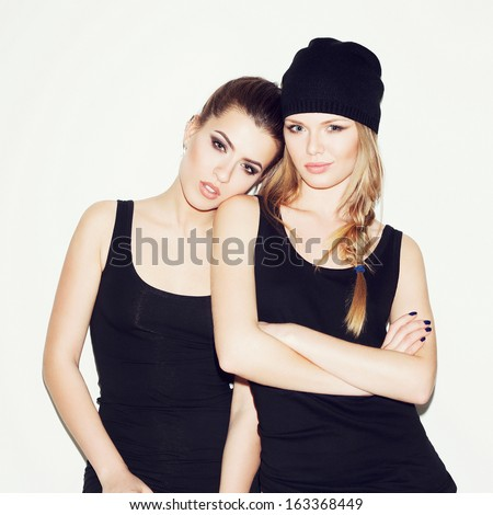 Two young girl friends standing together. Brunette put her head on the blonde's shoulder. Both looking at camera. Inside. White background - stock photo