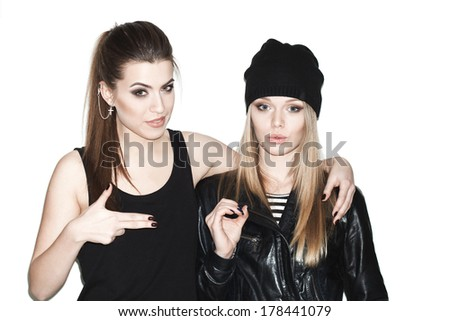 Two young girl hipster friends standing together, having fun.  indoor