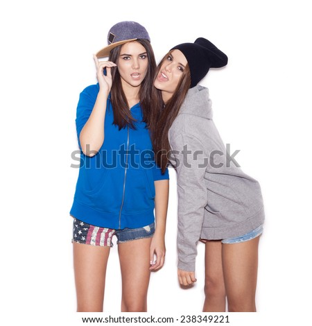 Two young girl hipster friends standing together, having fun.  indoor portrait. White background not isolated - stock photo