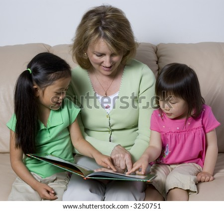 Two young girl learns to read with the help of a mother. - stock photo
