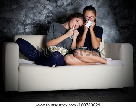Two young girl looks TV at dark room - stock photo