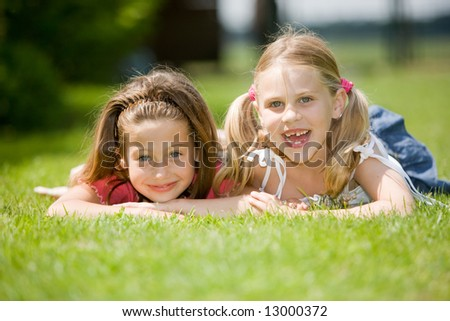 Two young girl lying together in the grass on a summer day - stock photo