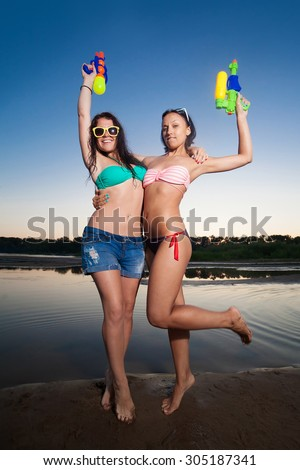 Two young girl posing with water pistols - stock photo