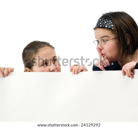 Two young girl trying to spy over a white wall, isolated against a white background - stock photo