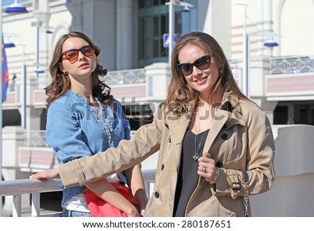 Two young girlfriends in front of shopping mall entrance - stock photo