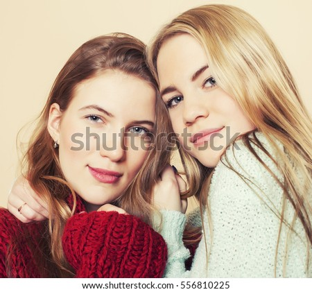 Two young girlfriends in winter sweaters indoors having fun. Lifestyle. Blond teen friends close up