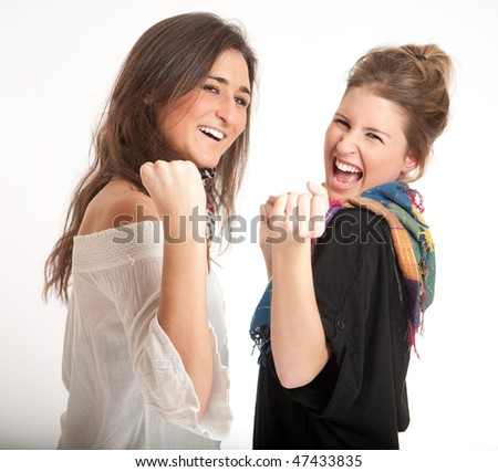 Two young girls, a blonde and a brunette happily celebrating - stock photo