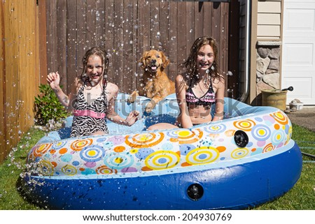 Two young girls and their pet Golden retriever playing in an inflatable swimming pool during the summer - stock photo