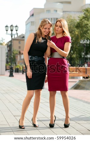 Two young girls are looking on mobile phone. - stock photo