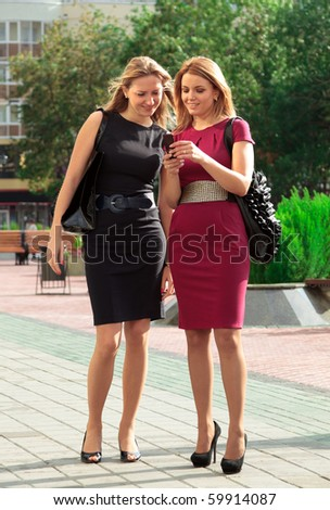 Two young girls are looking on mobile telephone.