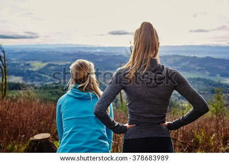 two young girls backs to camera looking out at landscape during sunset - stock photo