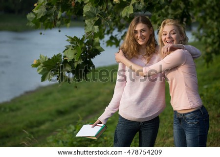 Two young girls best friends hug and smile on summer day near river in green park