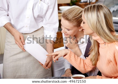 Two young girls choose in the dish menu - stock photo