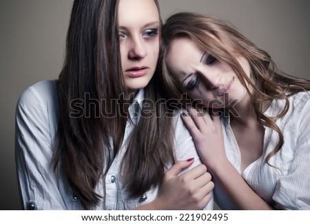 two young girls crying, studio shoot - stock photo