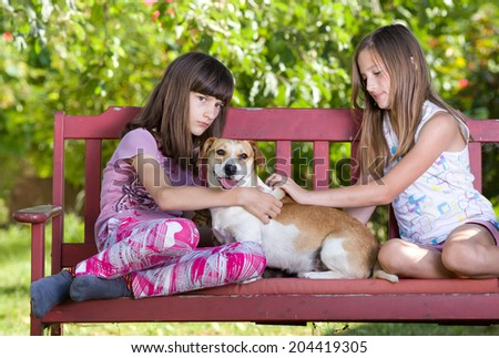 Two young girls cuddling cute dog on bench in park - stock photo