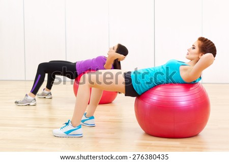Two young girls doing gymnastic exercises at sports hall - stock photo