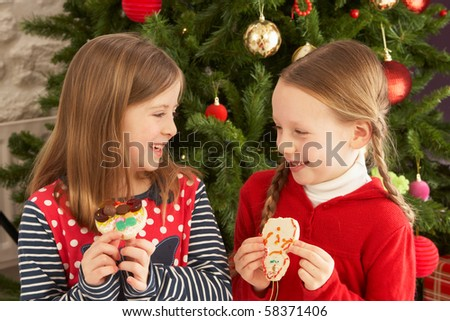 Two Young Girls Eating Cookies In Front Of Christmas Tree - stock photo