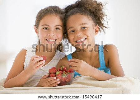Two young girls eating strawberries in living room smiling - stock photo