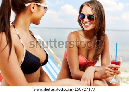 Two young girls enjoying rest on the beach - stock photo
