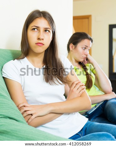 Two young girls friends sitting on the coach discontent and having an argument - stock photo